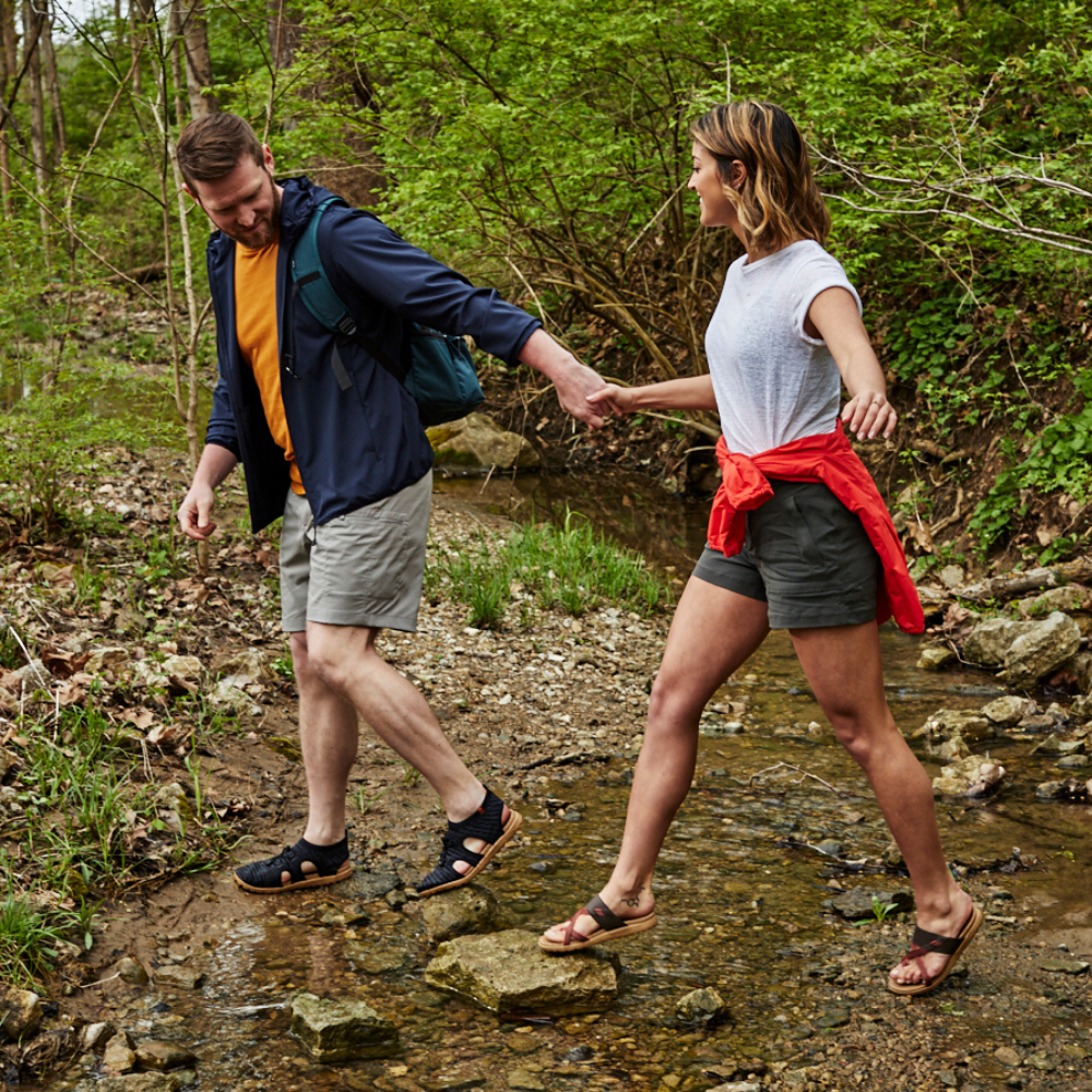 Men's and Women's Everywear Sandals. Male model wearing Casco walking on rocks. Female model wearing the Riley walking in the water