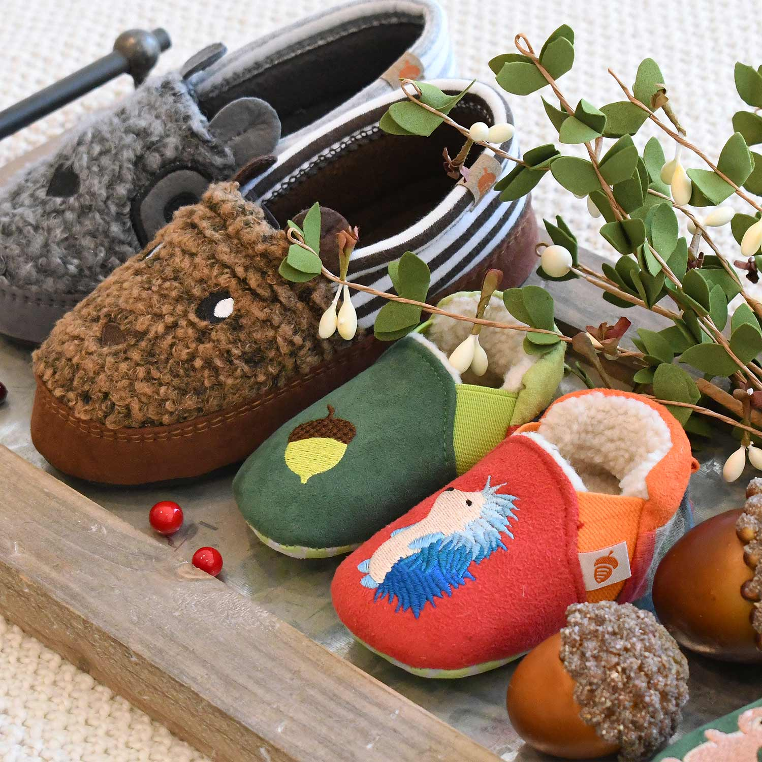 Selection of kids slippers on a tray with greenery - Acorn critter mocs and toddler easy-on slippers