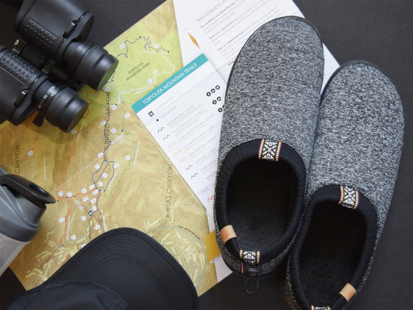 Grey Explorer shoes flatlay with maps, binoculars, hat and water bottle
