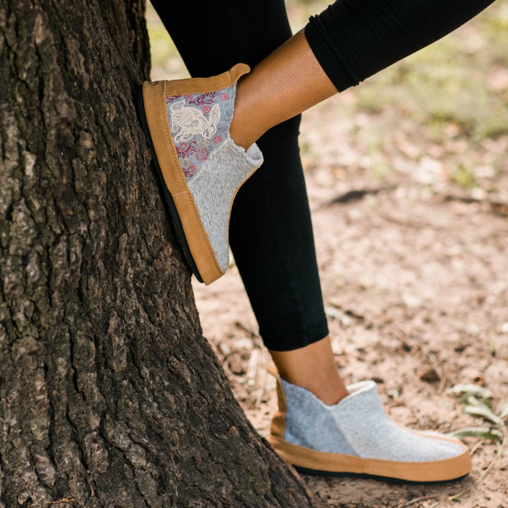 Women's Forest Bootie Slippers in Heather Grey Hare On Model Against A Tree