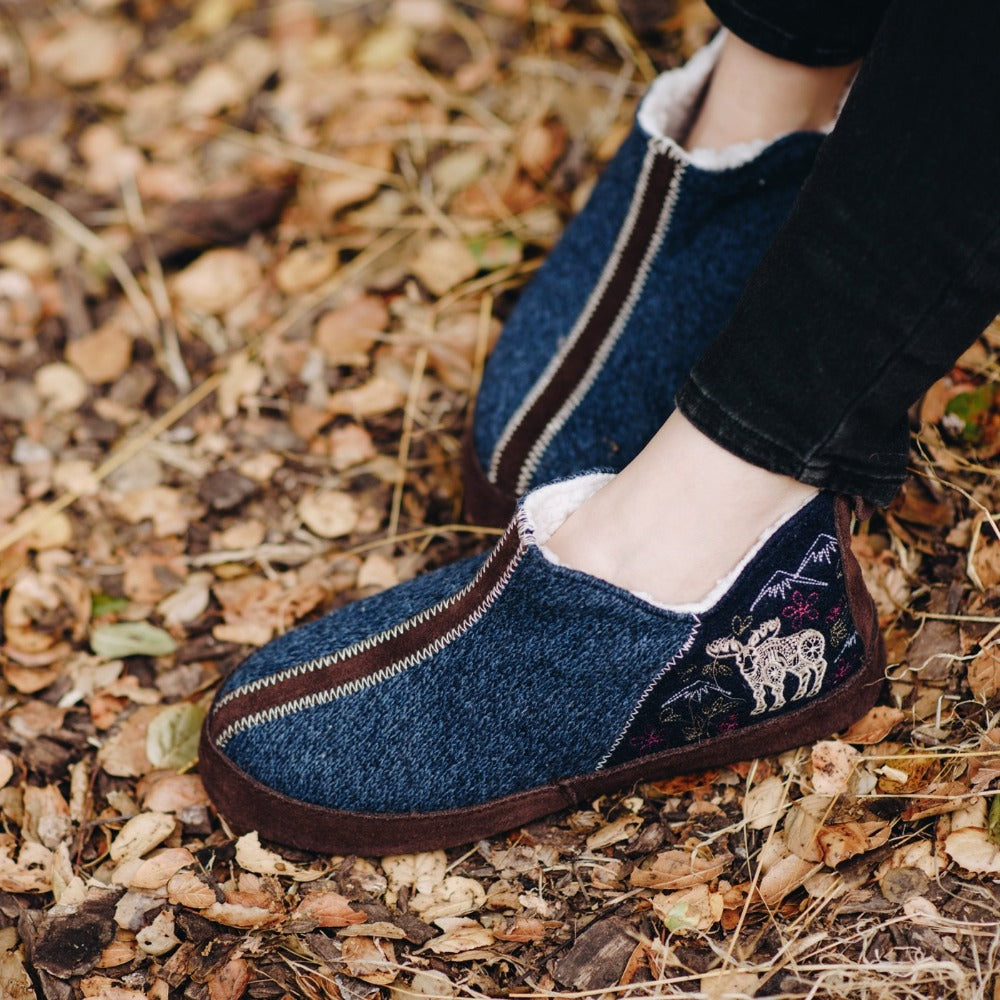 Women's Forest Bootie Slippers in Navy Moose on Model in a Bed of Leaves