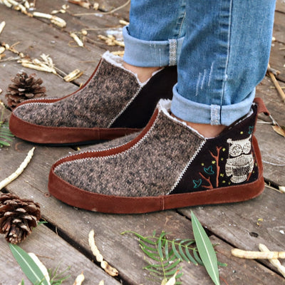 Women's Forest Bootie Slippers in Chocolate On Model with Leaves and Pine Cones