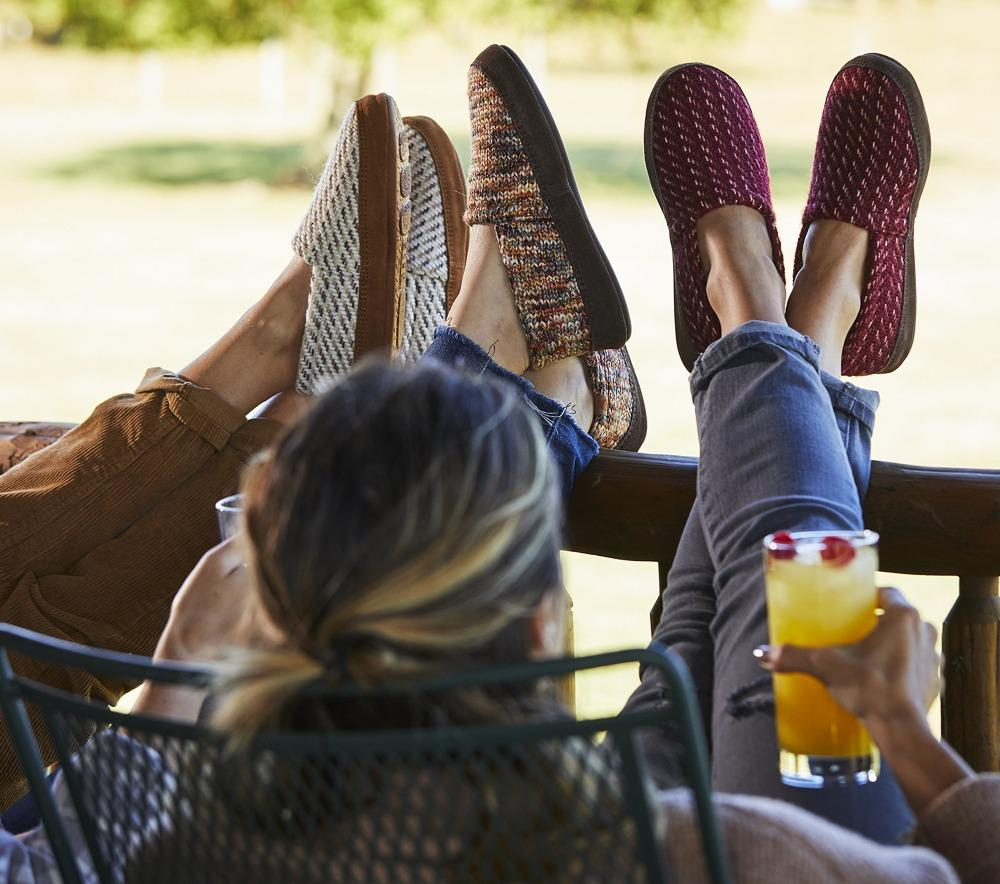 Women's Original Acorn Moccasins in Ewe, Garnet and Sunset all on model with their feet up on the porch fence