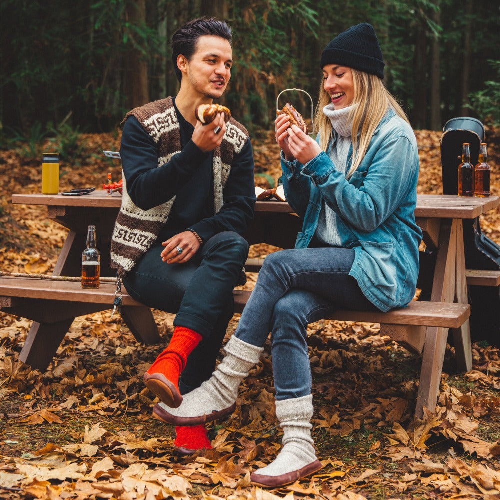 Male and Female model wearing the Grey and Red Ragg Wool Slipper Socks as they enjoy a meal together at their campsite