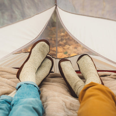 Male and Female model wearing the Acorn Slipper Sock in Grey Ragg Wool from the knee down while lounging in a tent