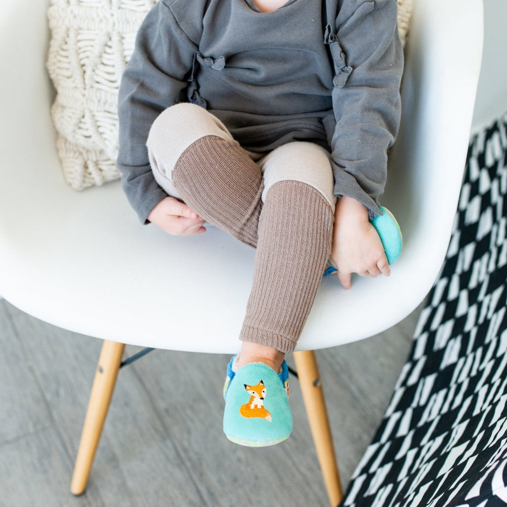 Toddler's Easy-On Animal Slippers in Teal Fox on Model Sitting in a Chair