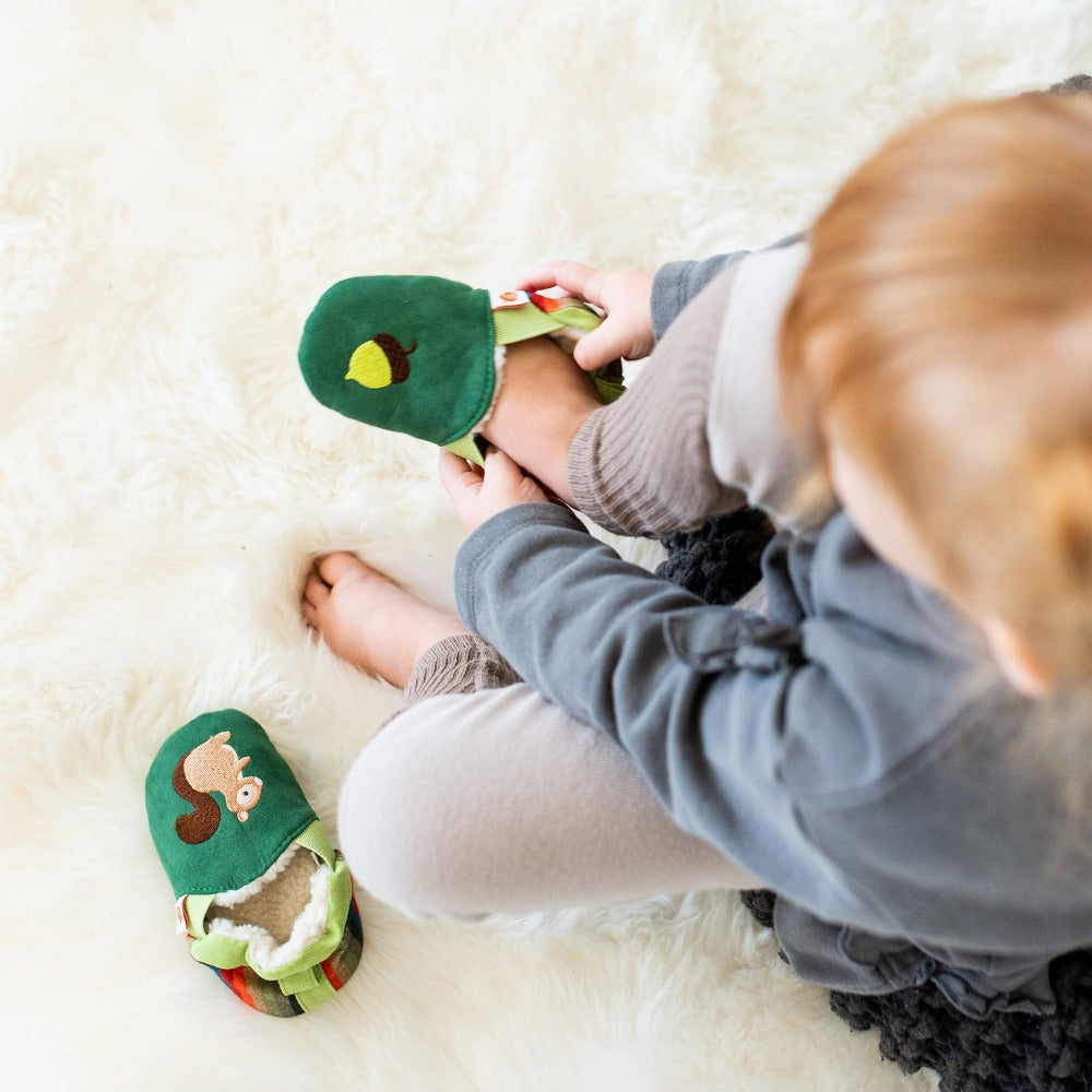 Toddler's Easy-On Animal Slippers in Green Squirrel Model Putting Them On Her Feet