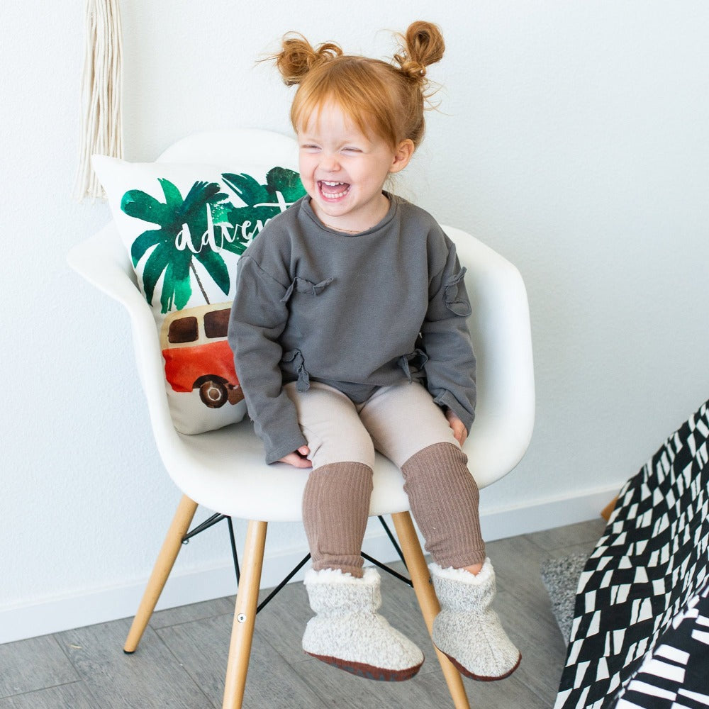 Toddler's Ragg Wool Booties in Grey Ragg Wool on Model Sitting in Chair Smiling