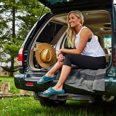 Women's Spa Thong Slippers in Peacock on Model Sitting in Back of Car