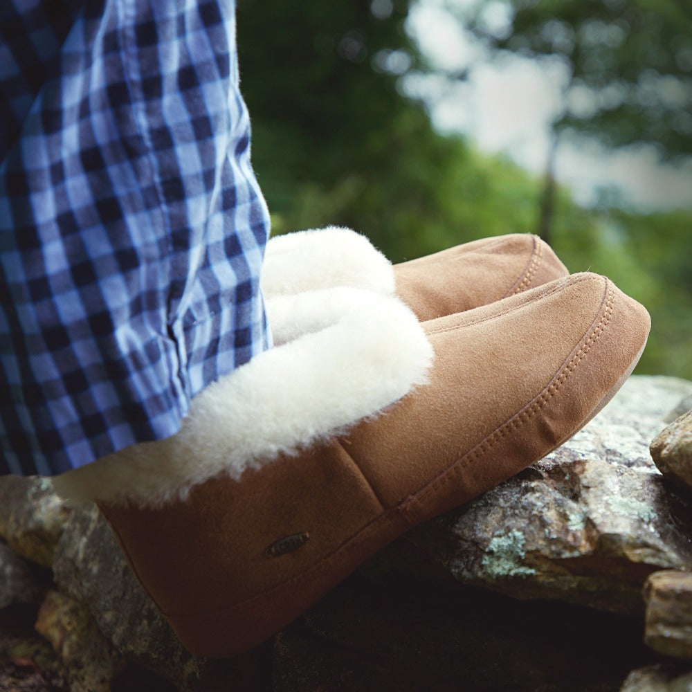 Men's Genuine Sheepskin Slipper Boot on figure wearing Pj pants sitting on rocks outside