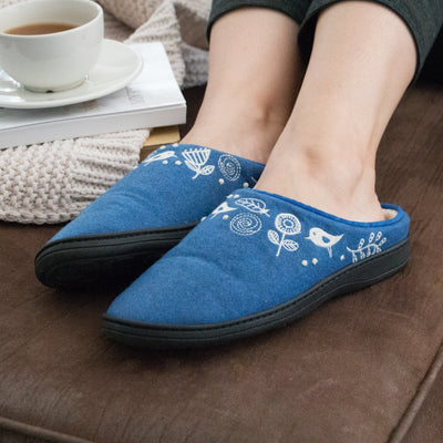 Women's Talara Mule Slippers in blue on figure laying back on comfy couch with coffee