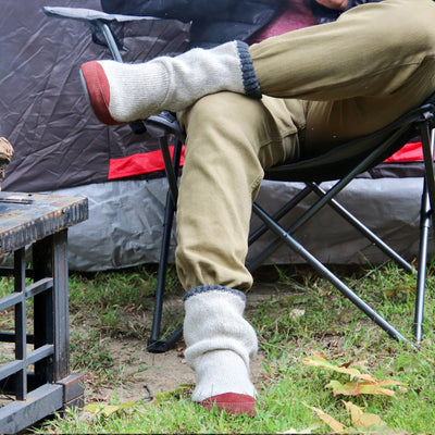 Men's Slouch Boots in Grey Ragg Wool On Model Sitting in Camping Chair by a Tent. Indoor / Outdoor Slipper Sock