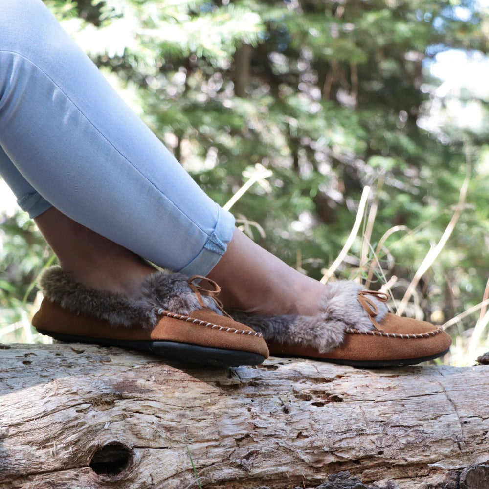Women's Faux Fur Moccasins on figure sitting on log outside in woods