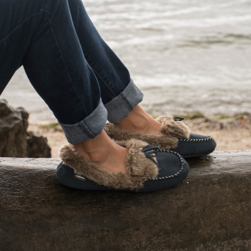 Women's Faux Fur Moccasins on figure sitting on log outside by water