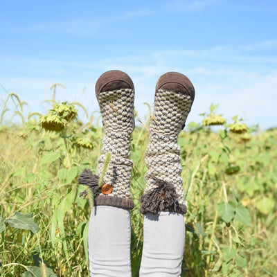 Women's Jam Tassel Boots on figure with legs kicked up in sunflower field