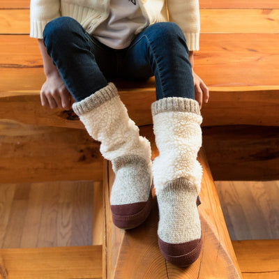 Kid's Slouch Boot Slippers on figure sitting on wooden table inside cabin
