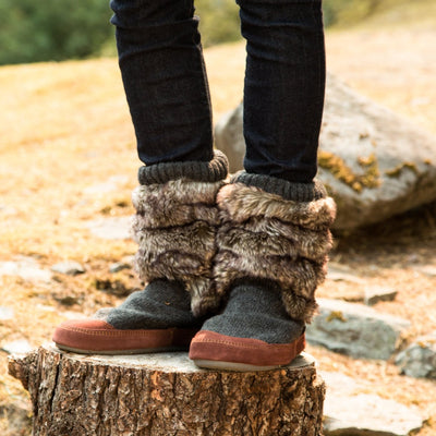 Kid's Slouch Boot Slippers on figure standing on stump in woods