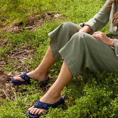 Women's Flora Suede Spa Thong Slippers on figure sitting down in grass against a tree