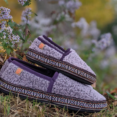 Kid's L'il Woven Trim Moccasins resting in grass in woods by wild flowers