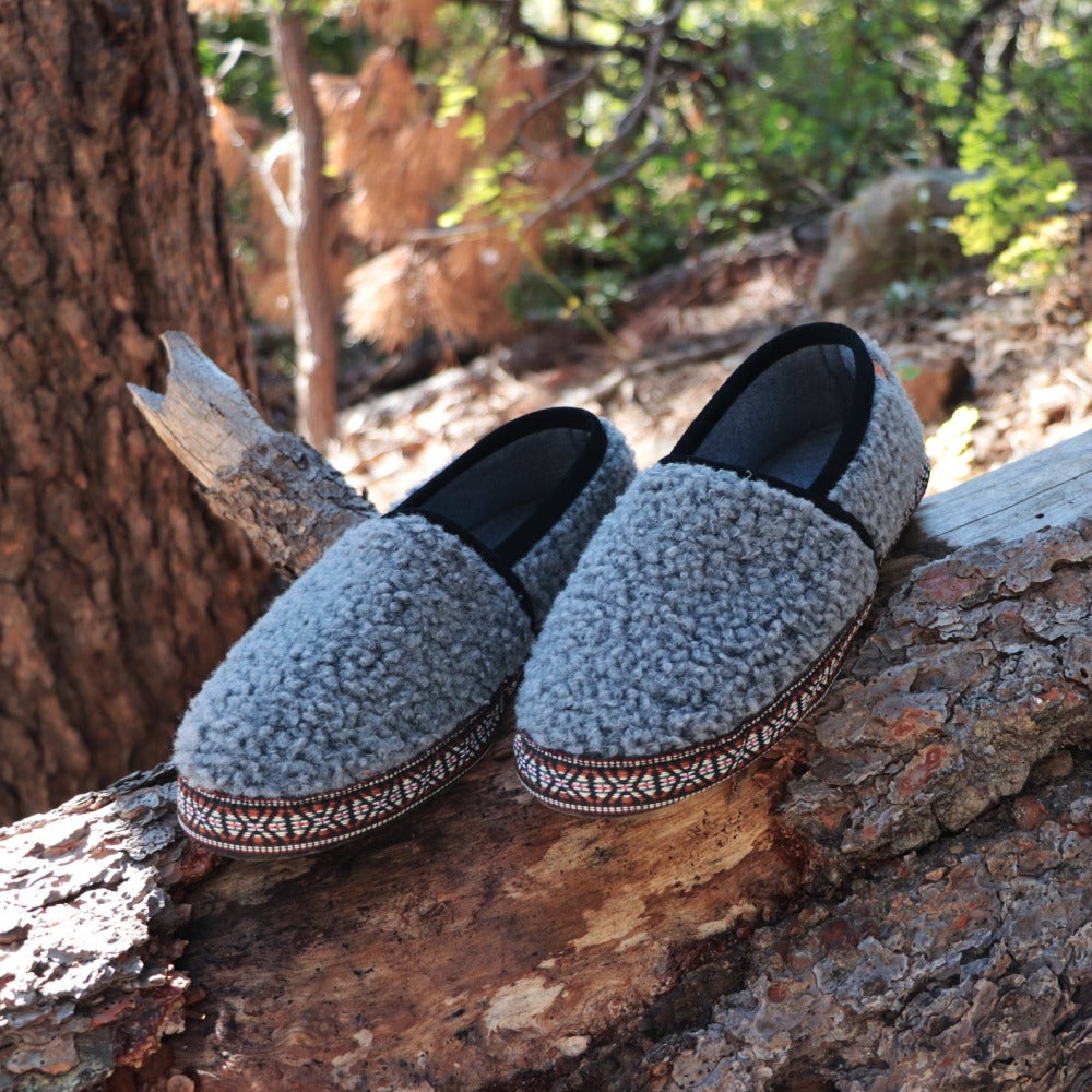 Men's Woven Trim Moccasins off figure resting on a log in the woods