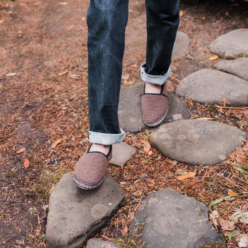 Men's Woven Trim Moccasins on figure walking on stones through the woods