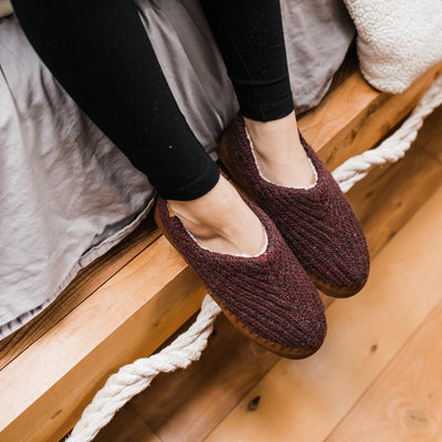 Women's Recycled Camden Moccasins in garnet on figure sitting on the side of a bed