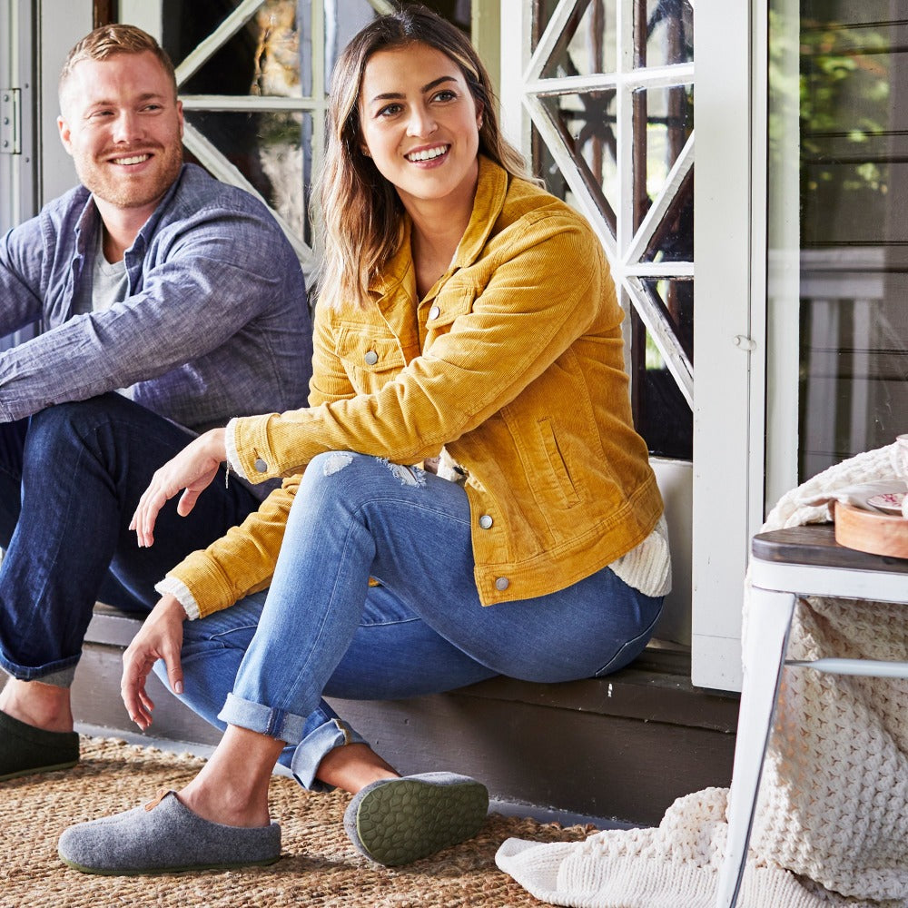 Women's Parker Hoodback Slipper + BLOOM™ in Ash Grey on model sitting on a porch with a male model
