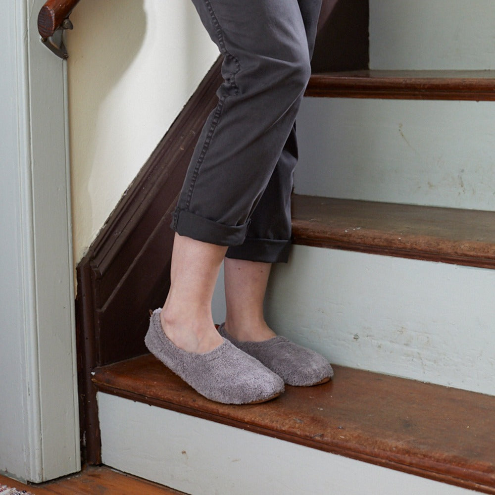 Women's Spa Travel Slipper in Grey On Model Standing on Stairs