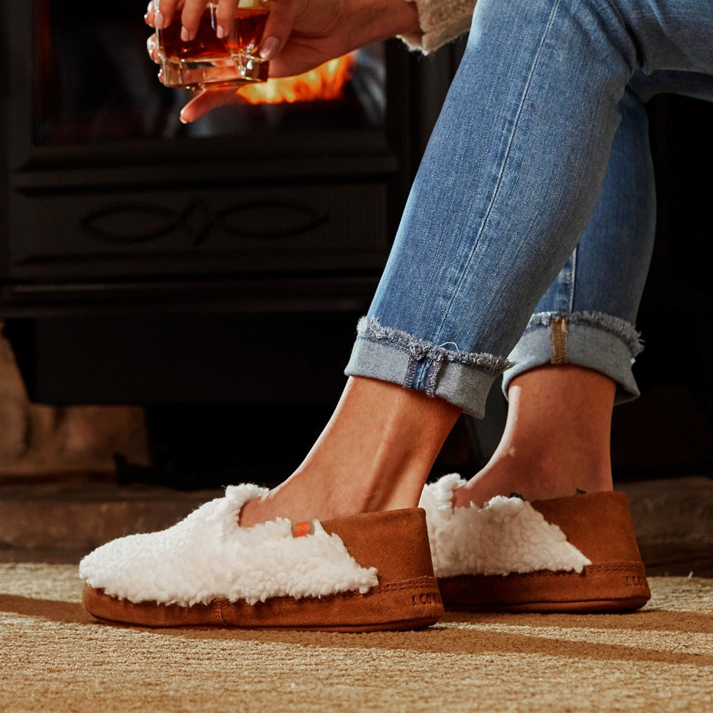 Women's Acorn Moc with Collapsible Heel Slipper in Buff Popcorn on model sitting by a fireplace with a drink in her hand