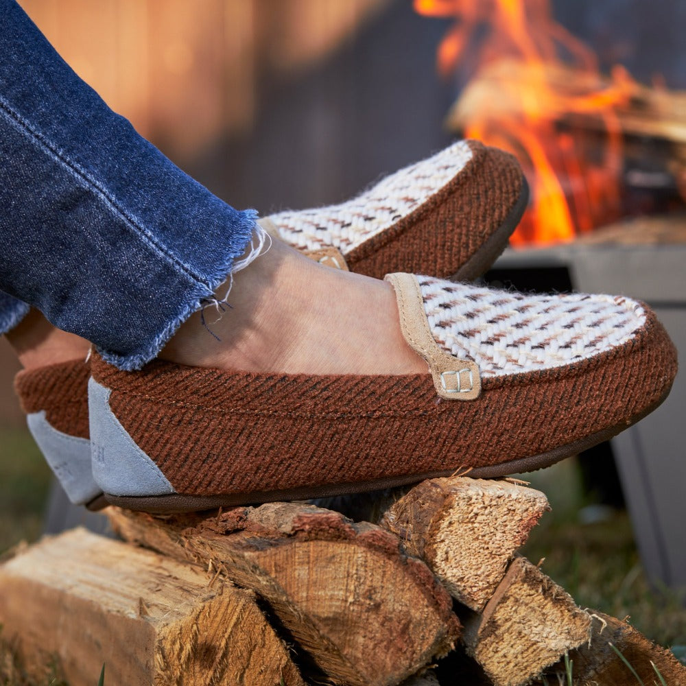 Women's Andover Driver Moc Slipper in Buckskin sitting on a pile of wood with a campfire in the background