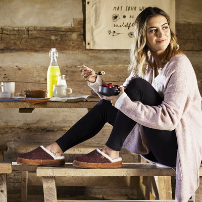 Women's Recycled Camden Clog in Garnet on model sitting at a rustic table eating fruit with her feet up on the dining bench
