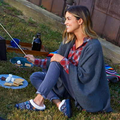 Women's Fairisles Hoodback Slipper in Blue Multi with different hues of blue and tan on model sitting in front of a barn roasting marshmellows