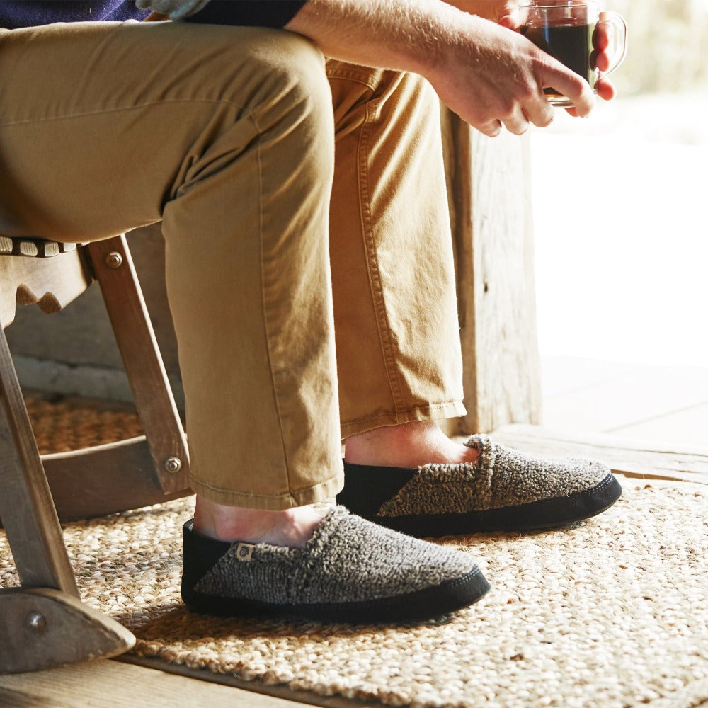 Men's Acorn Moc with Collapsible Heel Slipper in Earth Tex on figure. Man sitting in rocking chair near a doorway with a mug of coffee in his hands