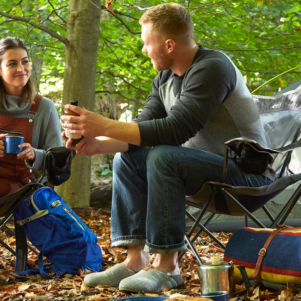 Men's Parker Plaid Hoodback Slipper + BLOOM™ in Grey Plaid on male model sitting with a female model at a campsite drinking coffee