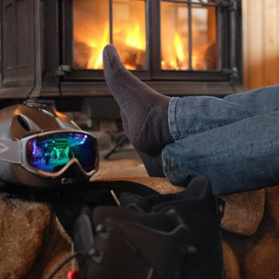 Man by Fire after Snowboarding in cozy cabin wearing charcoal versafit socks