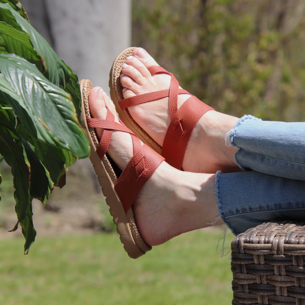Women's Everywear Riley Sandal in Copper on model with her feet dangling over a wicker chair