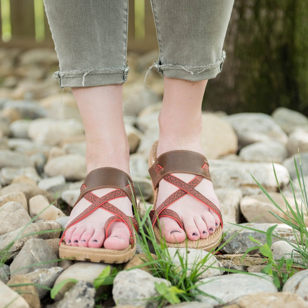 Women's Everywear Riley Sandal in Walnut on figure standing on several rocks