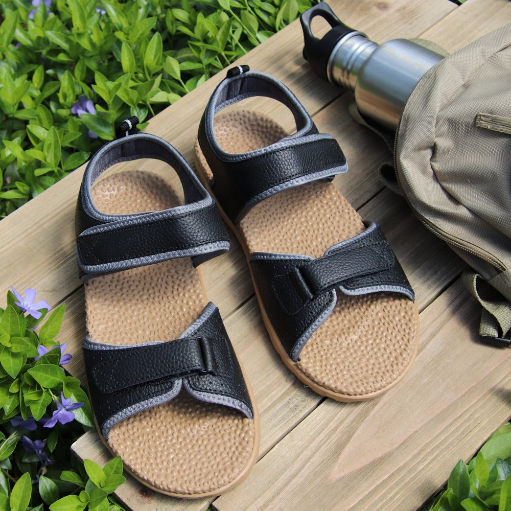 Women's Everywear Grafton Sandal in Black sitting on bench in lush greenery with a backpack and a water bottle