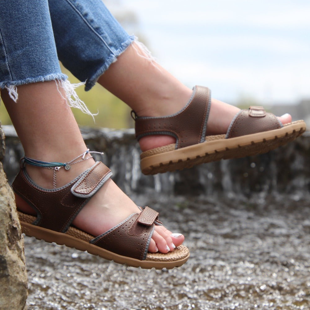 Women's Everywear Grafton Sandal in Walnut on figure with a river waterfall behind