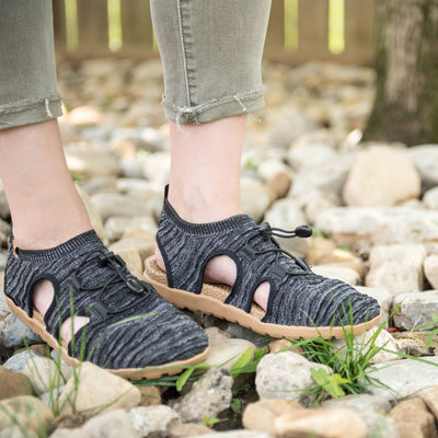 Women's Recycled Casco Everywear Sport Sandal in Black Heather on figure standing on rocks