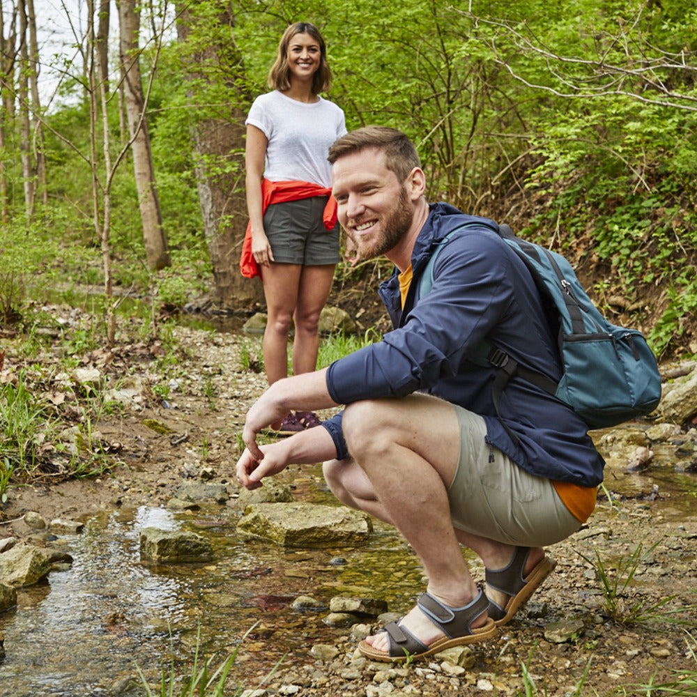 Men's Everywear Grafton Sandal in Walnut on model skipping stones in a creek with a female model in the background