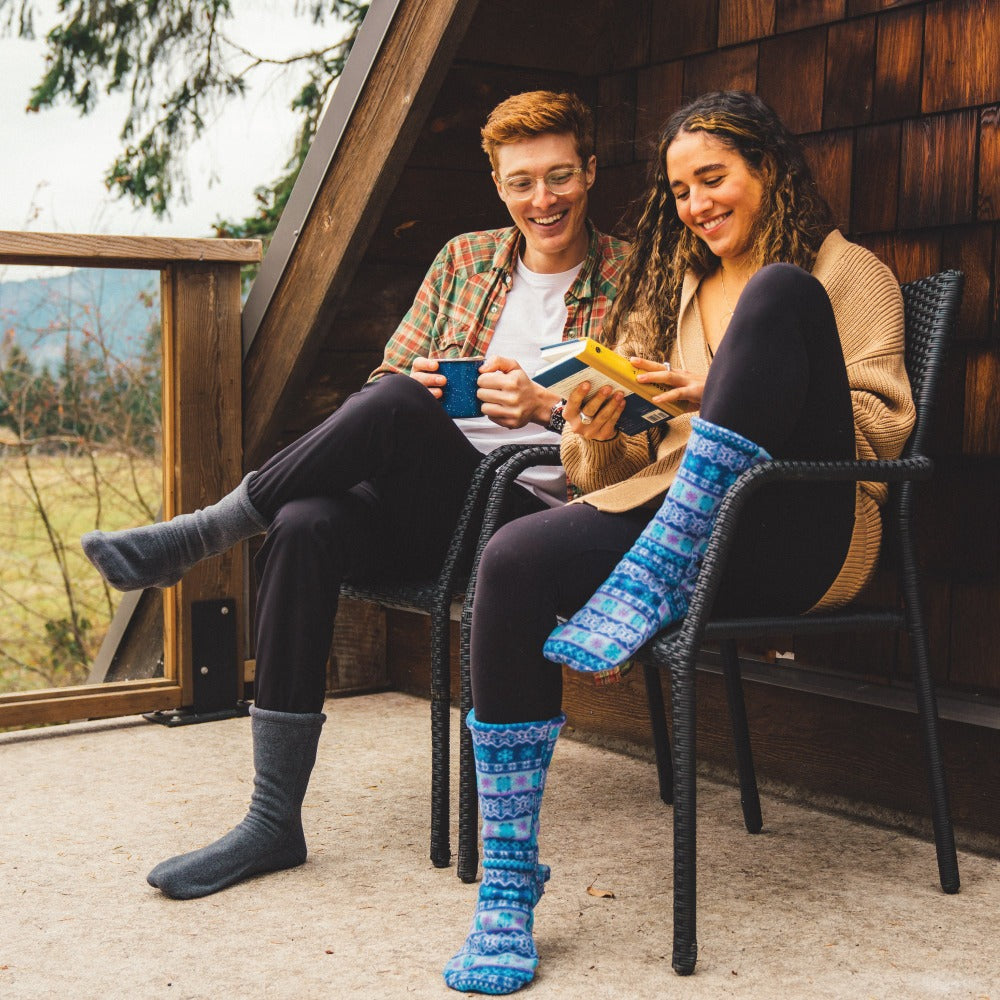 Couple sitting out on a porch wearing the Charcoal and Icelandic Blue Versafit socks. Reading and sipping coffee.