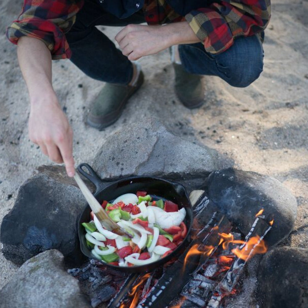 Acorn Men's Rambler Moc worn by male model cooking stew at campside beach fire