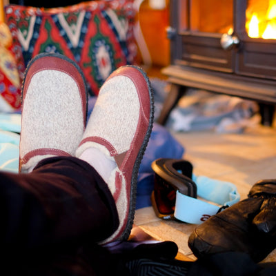 Men's Fleece-Lined Rambler Slippers on foot with feet propped up in front of fire