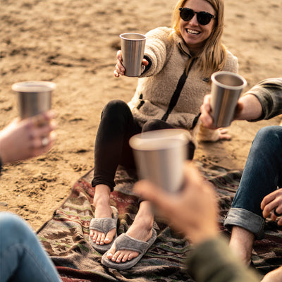 Women's Spa Thong Slippers in Grey on figure. Model wearing slippers is smiling and holding up a glass on the beach. Friends surround here, all cheers-ing