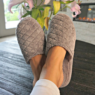 Women's Spa Quilted Clog in Grey on Figure with feet up on dining table with flowers and fireplace in the background