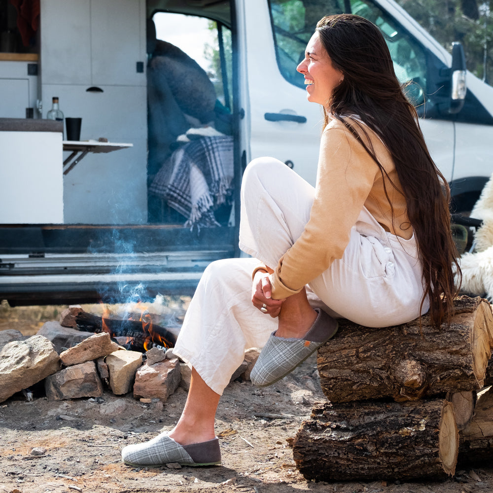 Women's Algae-Infused Parker Slippers on figure. Model sitting on a pile of wood around a fire. A converted van is behind her. She is laughing and having a good time in her slippers.