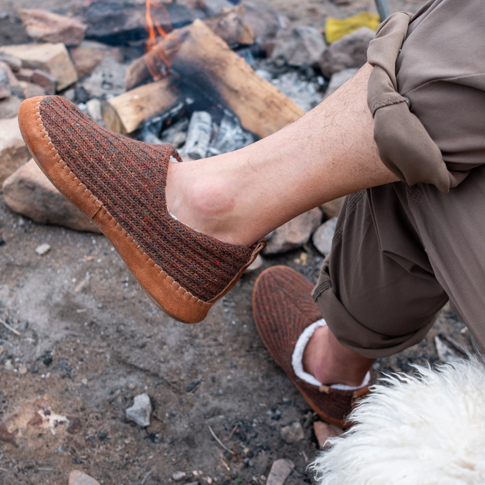 Men's Sustainable Camden Moccasins on figure. Male model sitting with his legs crossed in front of a fire.
