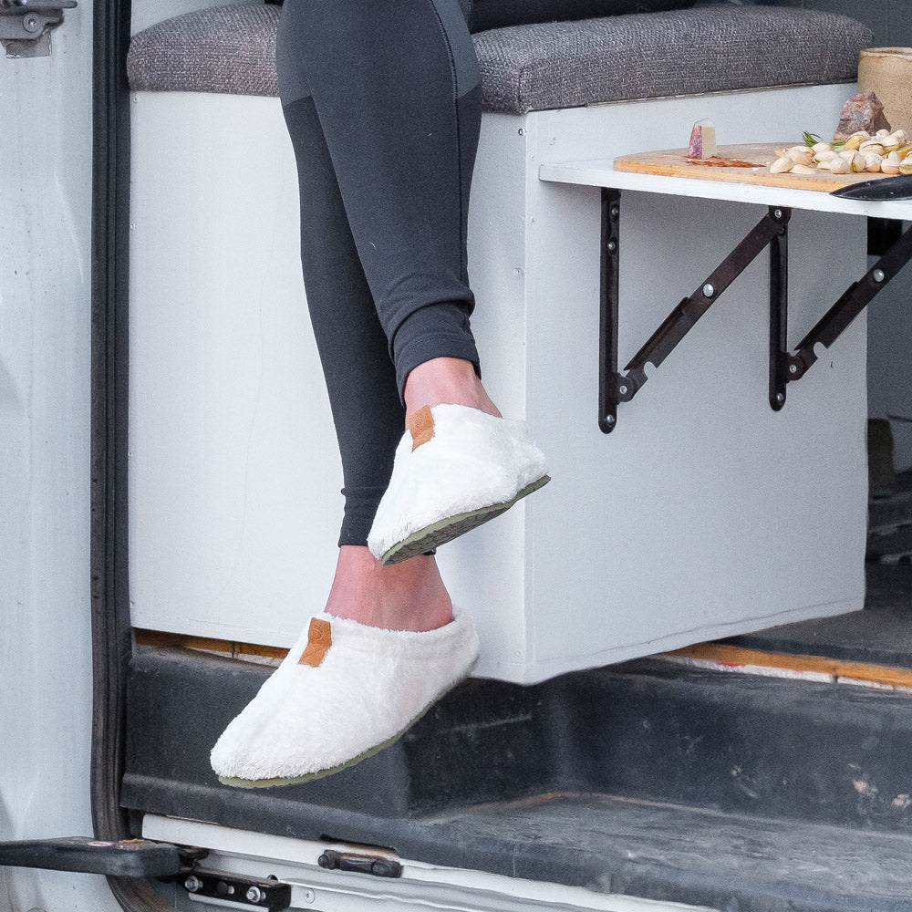 Women's Algae-Infused Spa Slippers in Ewe on figure. Model sitting on seat in converted van with a charcuterie board next to her