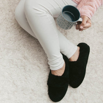 Women's Adjustable Spa Wrap Slippers in Black On Model Sipping Coffee on Fur Rug
